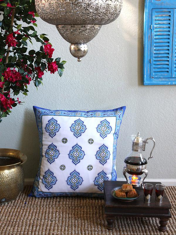 white and blue pillow in a Moroccan pattern