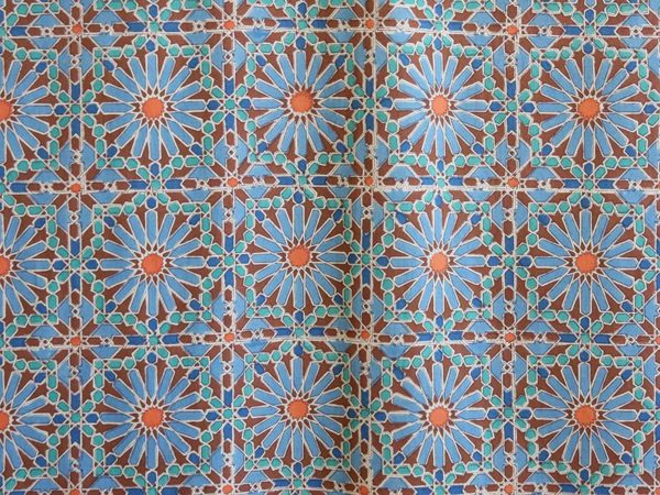 A fabric swatch in a tile mosaic print with blue and orange flowers