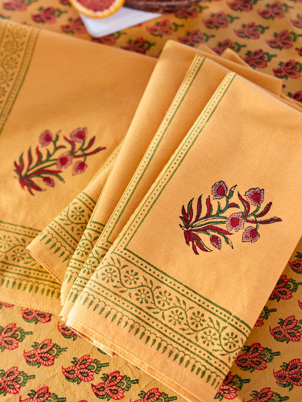 Orange summer cloth napkins lay upon beautiful orange summer tablecloths