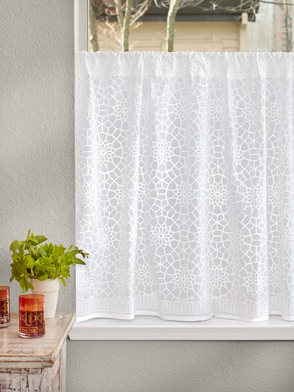 A white cafe curtain hangs at the bathroom window