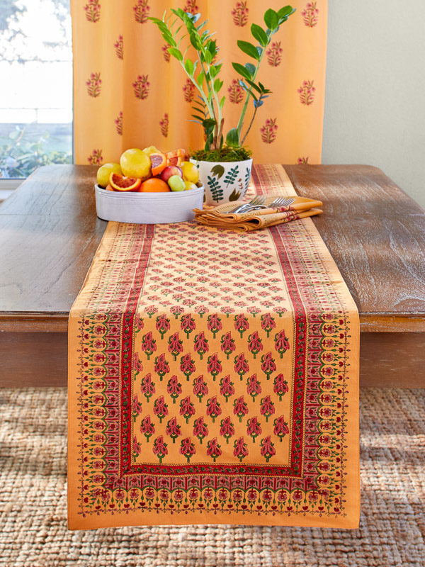 red orange indian table runner on wood table with fruit