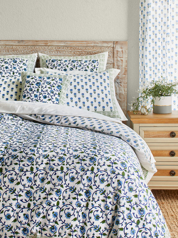 A bedroom with a white, green, and blue floral duvet cover and bedding set