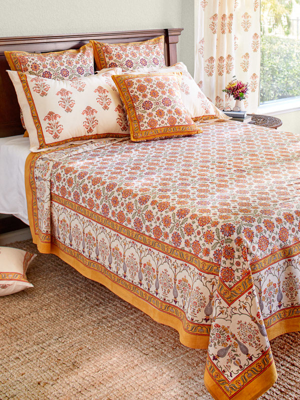 A queen size bed made with orange bedding and floral print
