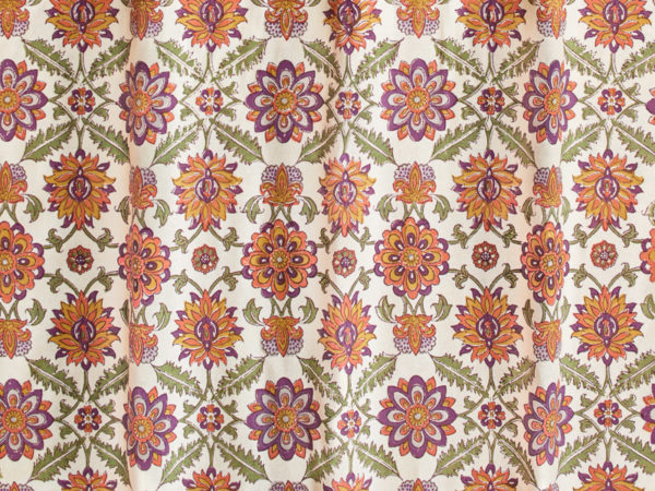 Green, plum, yellow, and orange floral print fabric swatch