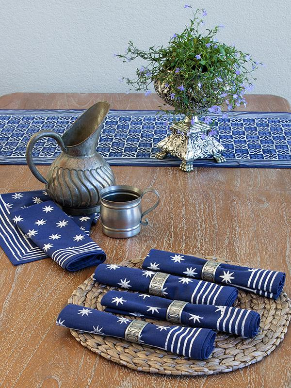 navy blue table decor with table runner, blue cloth napkins with star pattern wrapped in napkin rings on a placemat