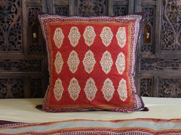 A red Indian print pillow propped up on a carved headboard