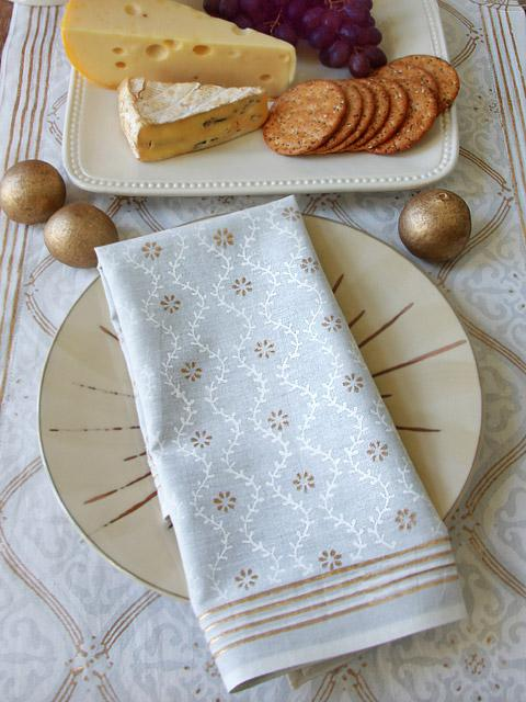 white and gold cloth napkins upon a white and gold tablelcloth with cheese and crackers at the side