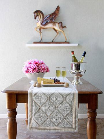 A white and gold table runner over a wooden table with champagne and snacks