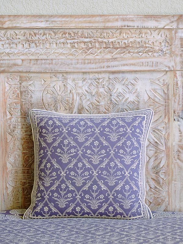 A lilac pillow with a flower print propped up against a whitewashed headboard