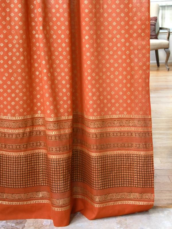 Orange curtain with gold Indian print skims the marble floor as orange home decor
