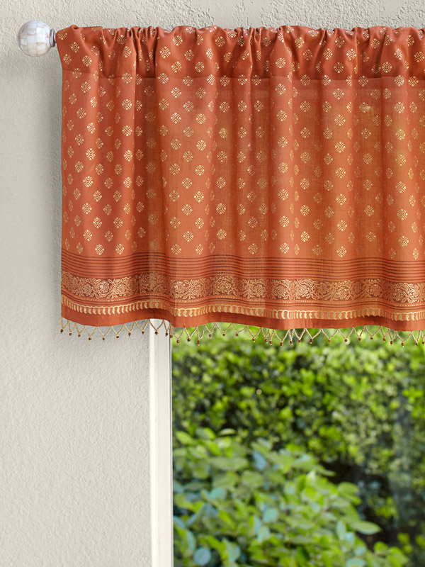 Orange valance with beading and gold embossing hangs at the bathroom window as orange home decor