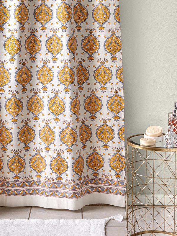Yellow and white shower curtain with French provincial print hangs in the bath.