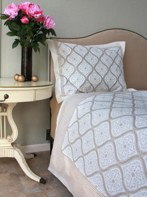 Gold and white bedspread with a vase of pink tulips at the nightstand.