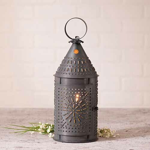 A rustic punched tin  lantern on the counter with white flowers behind it
