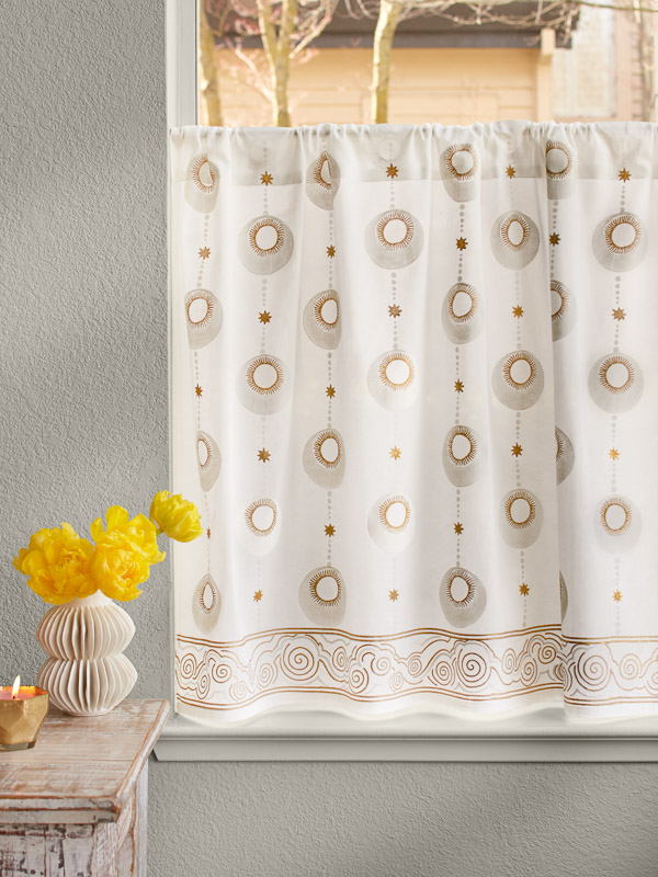 White and gold cafe curtain with a vintage pattern creates a bohemian window treatment.