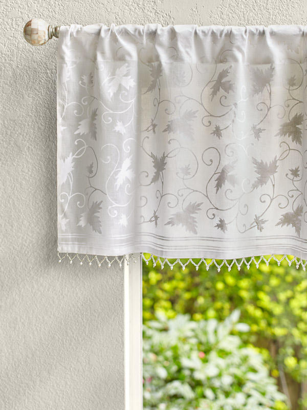 White patterned valance with beading tops a sunny window.