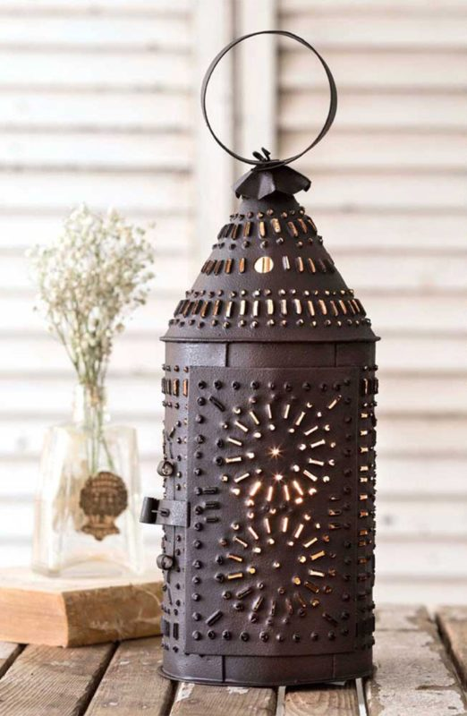 A tin lantern sits at a picnic table with a bouquet of white wildflowers, the ultimate in rustic home decor