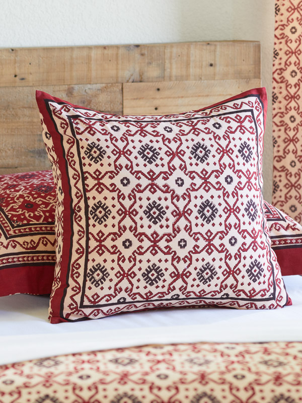 Cream red and black throw pillow rests on a bed in a rustic bedroom setting