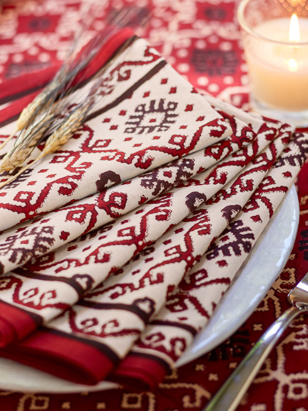 Red and black cotton napkins with a wheat bundle and candle help set a table with rustic home decor.