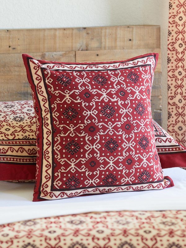 Red and black throw pillow on a bed looks as if it's in a rustic bedroom or bohemian bedroom