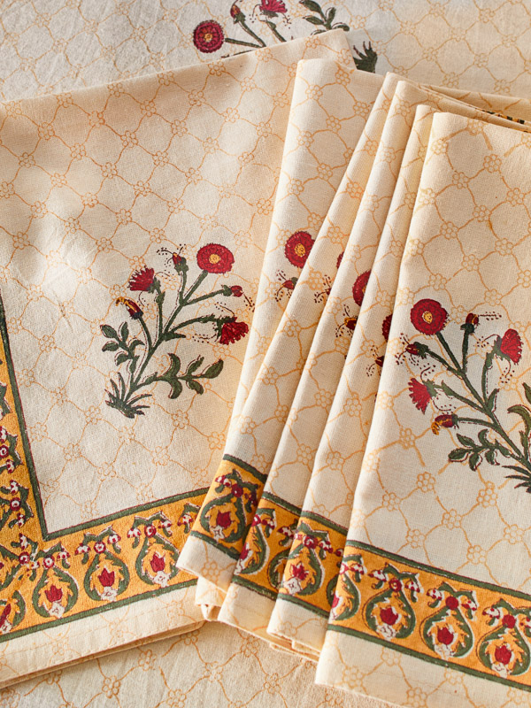 Cloth dinner napkins with a red flower look elegant at a table setting.