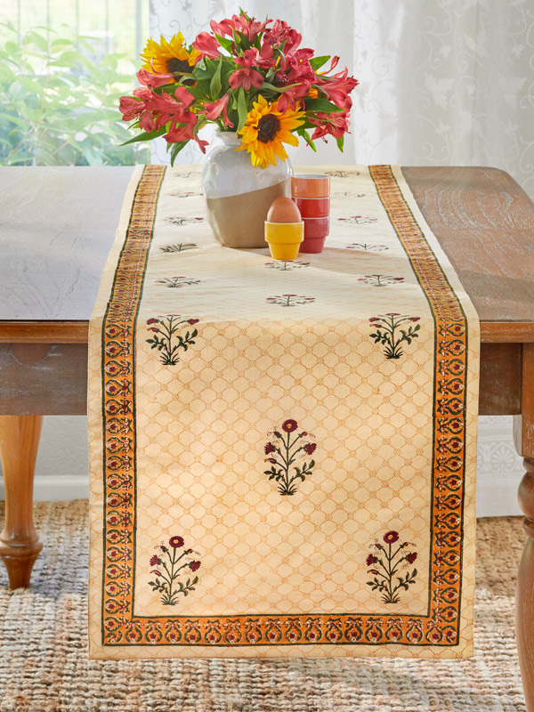 A vintage style red floral table runner with a sunflower centerpiece is beautiful farmhouse rustic home decor.