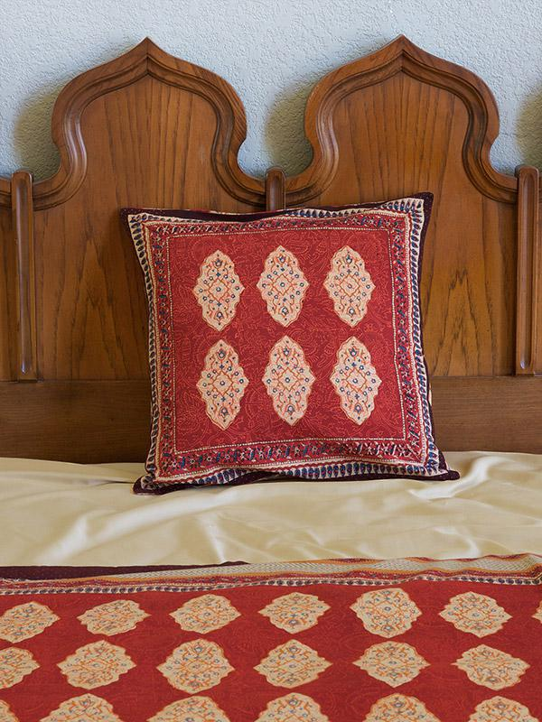 A red throw pillow makes for global rustic home decor when propped against a wooden headboard.