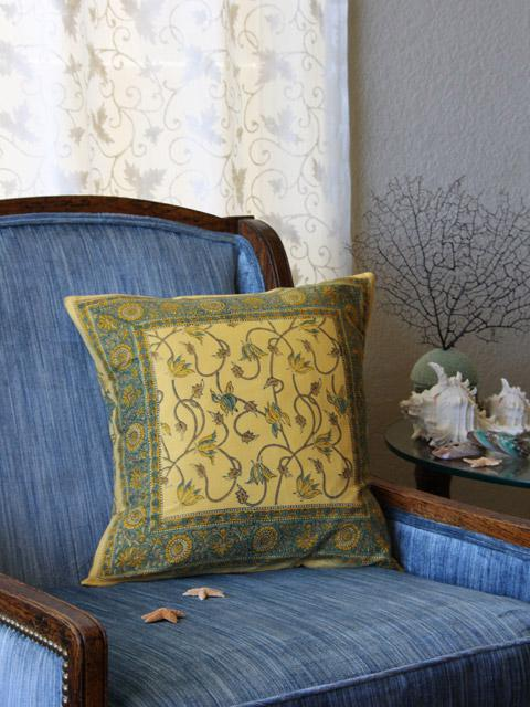 A yellow throw pillow with a botanical vine print rests upon a blue velvet side chair to add yellow into a room.