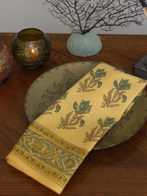 Yellow cloth napkin with palm trees lays on a china plate to add yellow in dining room spaces.