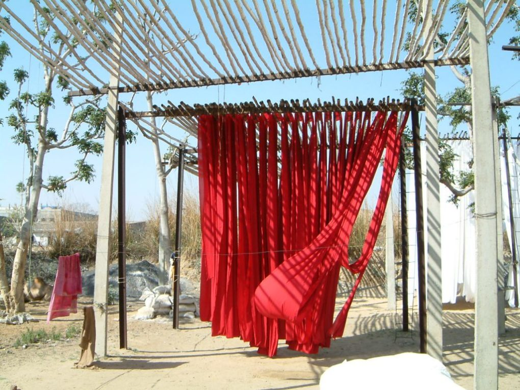 Red fabric dries in the sun before undergoing the block printing process