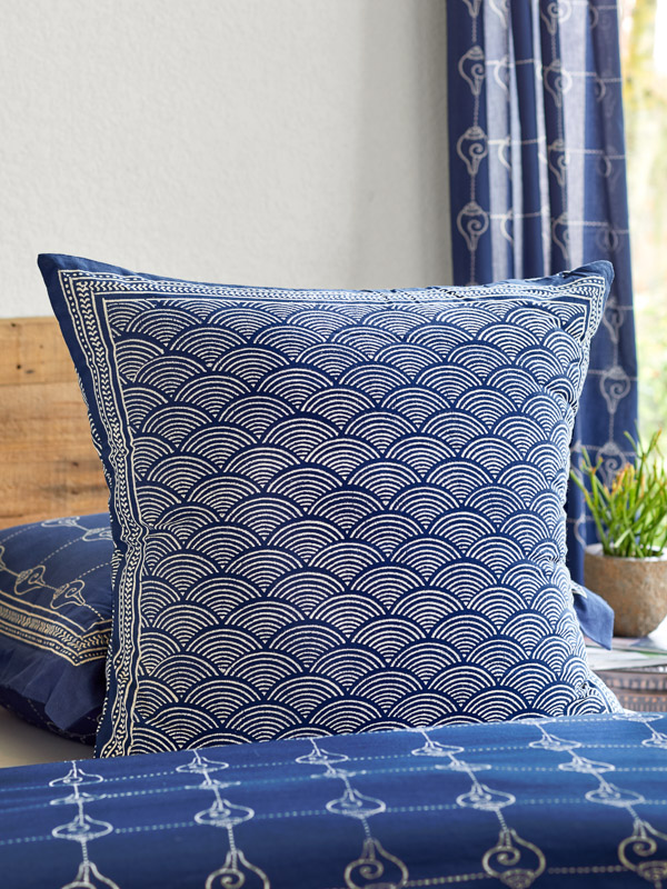 Dark blue pillow propped up in a zen room
