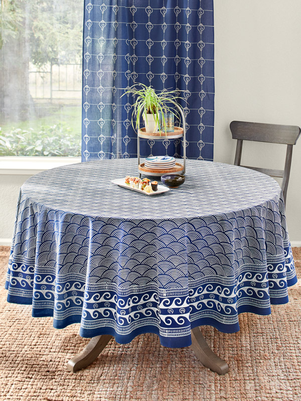 Sushi rolls and dishes are on a blue round tablecloth and a sisal rug in a zen room
