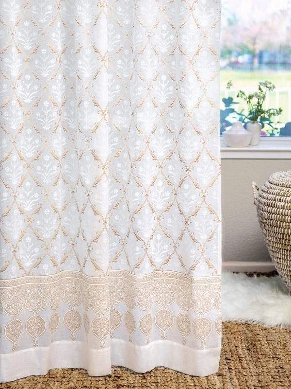 white and gold curtains hang in a neutral glam living room