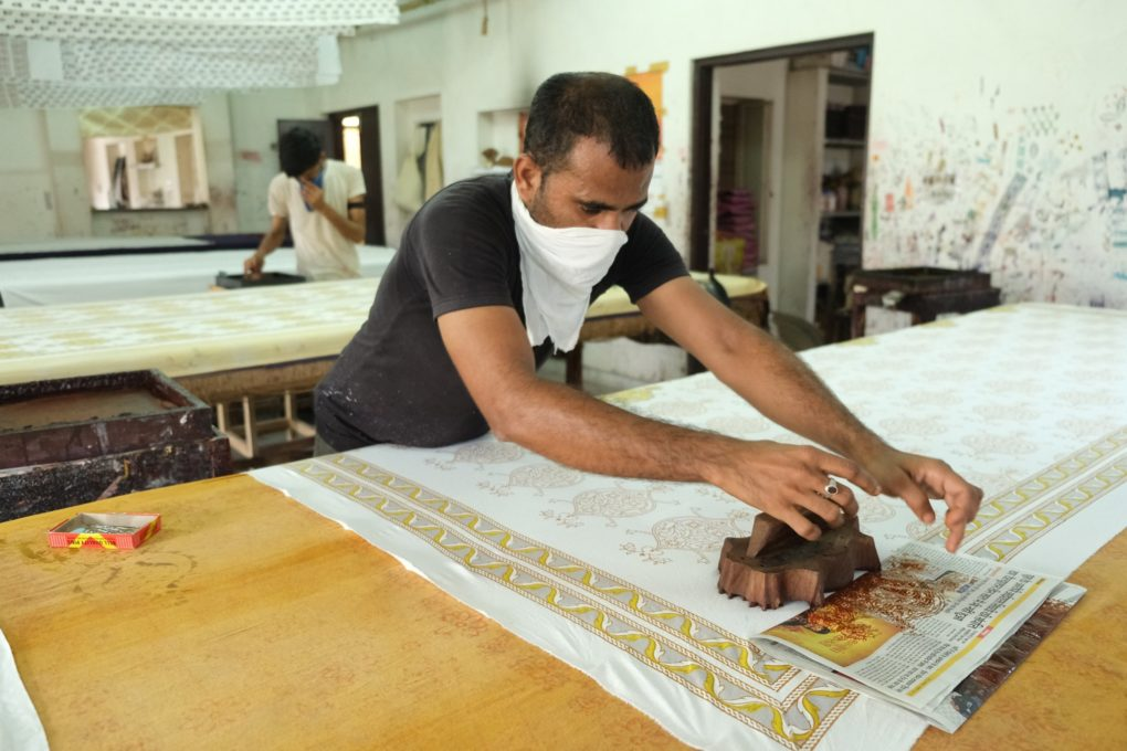 Artisan wears mask and adheres to safety measures while woodblock printing for a fair trade boutique
