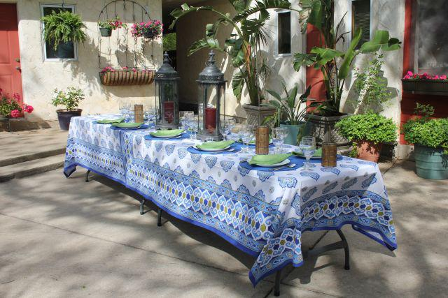 moroccan tablecloth, outdoor table setting with plants and lanterns set up for a party