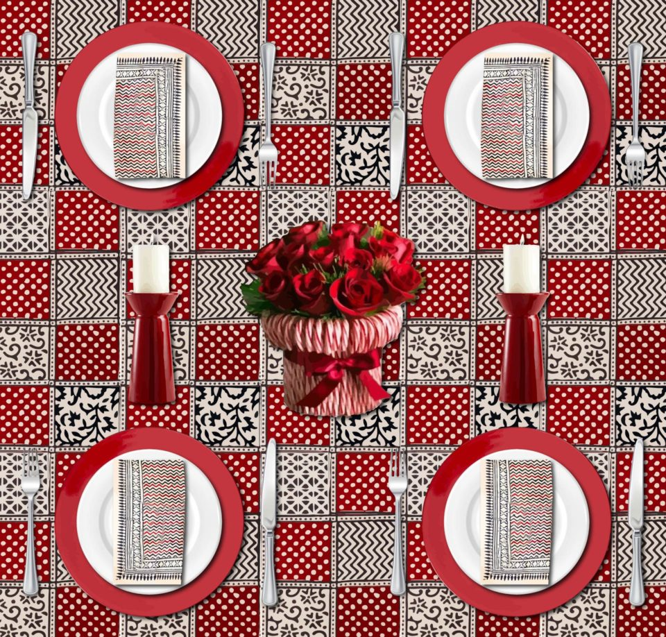 A colorful Christmas table set with a red Christmas tablecloth