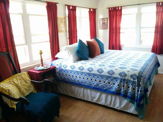 colorful Moroccan bedroom with blue and white Moroccan bedding, red curtain panels, Moroccan throw pillows