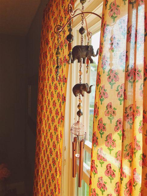 tangerine orange curtains with paisley print and elephant windchimes, bohemian home decor