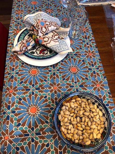 Moroccan blue table runner with geometric and floral pattern, cloth napkins, bowl of nuts