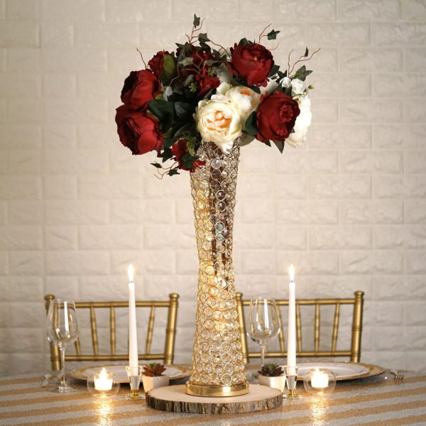 a gilded and jeweled tall vase filled with white and red roses upon a white and gold tablecloth at a romantic table setting for Valentine's Day