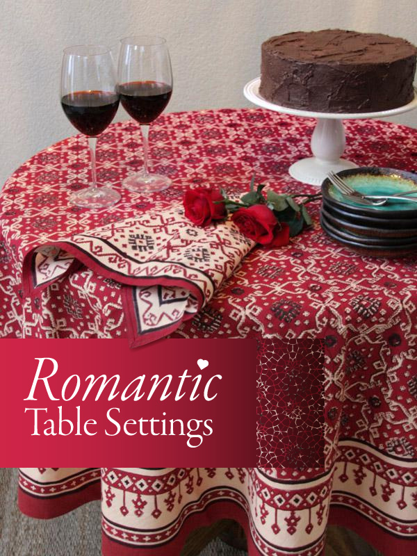 A red Valentine tablecloth set for a romantic table setting with red wine, roses, cloth napkins, and chocolate cake