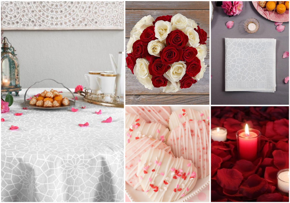 A white tablecloth styled for Valentine's Day table setting with red roses,  flower petals, candles, and heart-shaped tea cakes