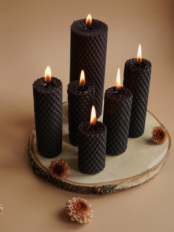 black candles with a honeycomb pattern impressed into the wax set upon a wood slice charger plate