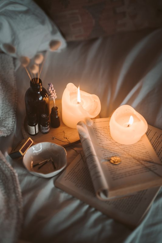 romantic bedding with candle light, flowers, wine and books in a hygge atmosphere