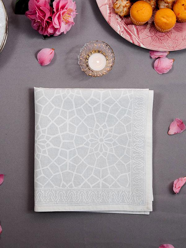 White cloth napkins with a Moroccan pattern like lotus flowers and trellis with pink petals on the table