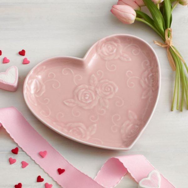 a pink heart-shaped plate, pink ribbon, and flowers upon a white Valentine tablecloth