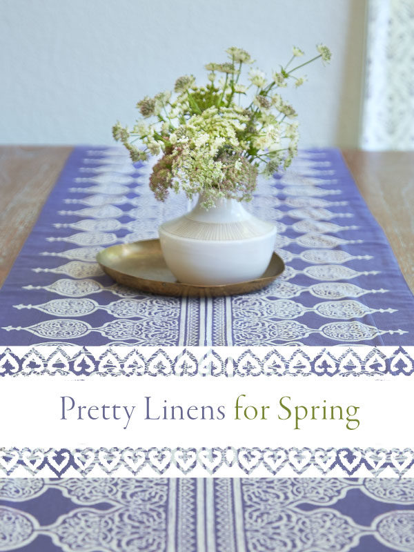 a pretty purple spring table runner with a white floral centerpiece in a white vase on a brass tray