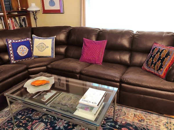 colorful block printed pillow covers brighten up a leather sectional couch