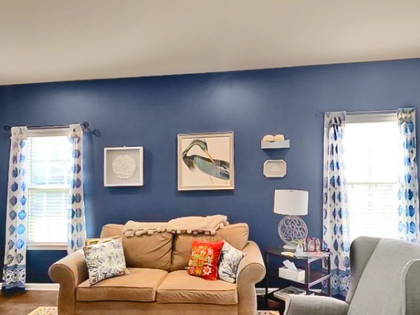 how to arrange pillows on a couch, white and blue moroccan curtains at the windows