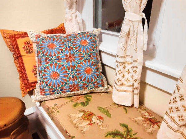 floral cushion covers on throw pillows on a window seat